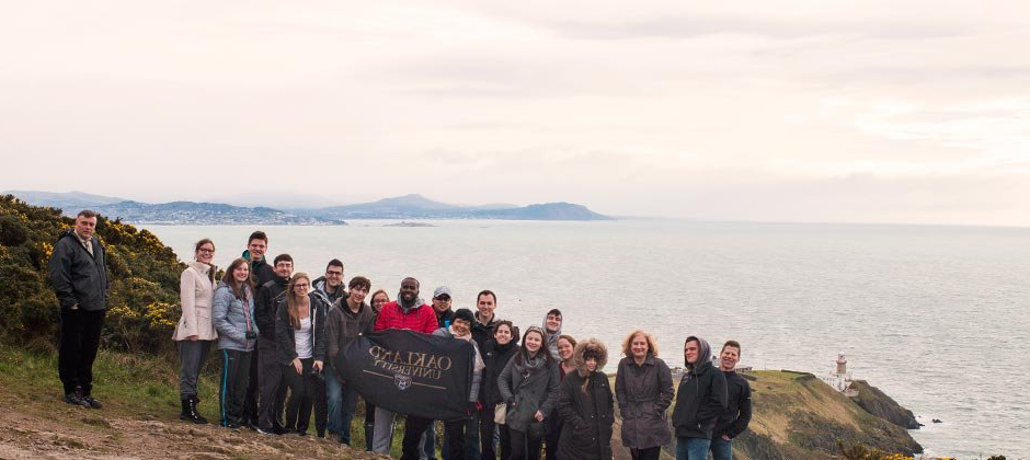 Group of ag体育app官网 students studying abroad standing infront of an ocean with an O U banner