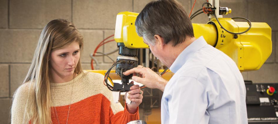 Female student and male instructor working on a robotic machine